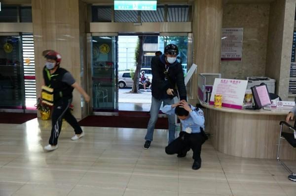 2名持槍歹徒闖入銀行,1名先控制保全人員,另名頭戴HELLO KITTY安全帽的歹徒身綁炸藥,大喊「搶劫、把錢交出來!不配合就引爆!」(記者陳恩惠翻攝)