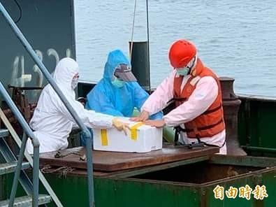 澎湖海巡隊及防檢局人員全副武裝,將船上豬肉以保麗龍密封帶走。(記者劉禹慶攝)