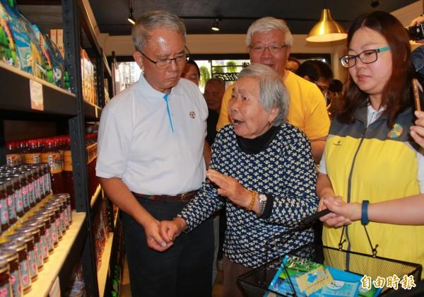 魏應充牽著老婦人的手陪同挑選食物。(記者陳冠備攝)