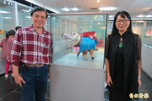 南投縣文化資產學會「豬」年生肖會員聯展,會員蕭璽(右)以廢棄物打造的「超人豬」,引人注目,圖左為學會理事長。(記者張協昇攝)