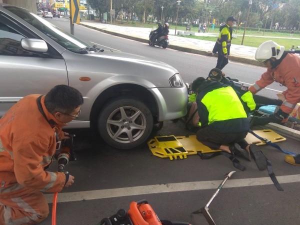 消防人員以千斤頂撐高轎車救出婦人。(記者蔡彰盛翻攝)