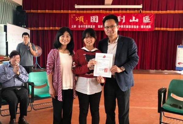 台中市圍棋協會理事長張耀中(右)、漢寶國小校長黃素珍(左)頒發結業證書給學生。(台中市圍棋協會提供)