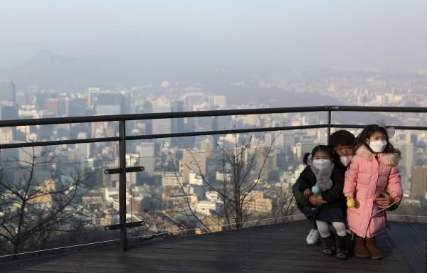 首尔市的「南山首尔塔」是南韩民众和外国观光客在首尔游玩的主要景点之一。图为一名父亲13日与他两名女儿合照时被迫戴口罩入镜,显示当地空污情况严重。(美联社)