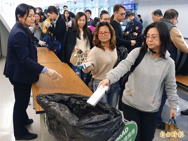 航警持續針對自中、港、澳來台班機旅客進行手提行李防疫檢查及宣導,許多旅客經宣導後都會主動將肉類製品丟棄。(記者朱沛雄攝)