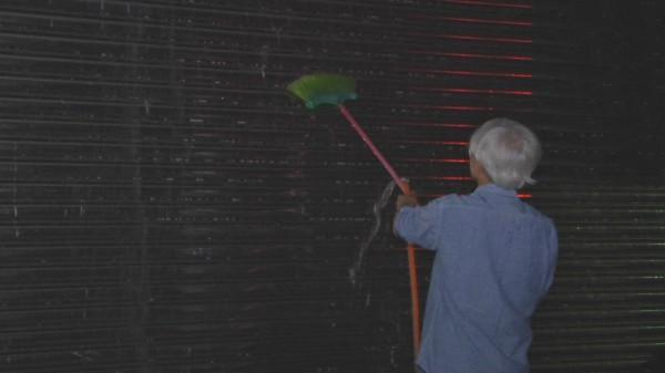托嬰中心員工用水柱沖洗沾滿蛋液的鐵門。(記者陳冠備翻攝)