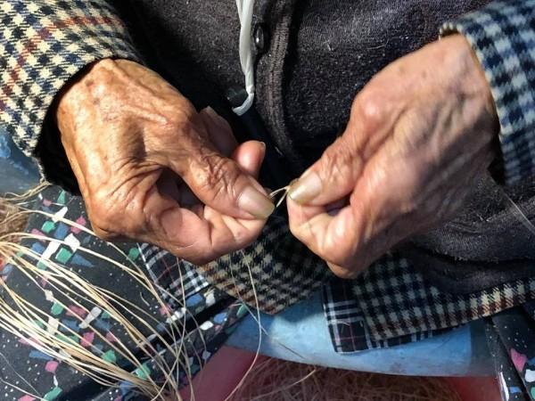 Ibay(潘烏吉)阿嬤充滿皺紋的雙手,高齡94歲還到香蕉絲工坊整理香蕉絲線。(新社香蕉絲工坊提供)