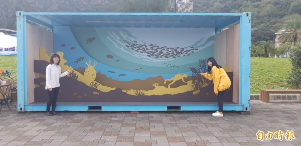 基隆市八斗子晨星碼頭邊,最近出現貨櫃裝置藝術,國立台灣海洋大學文創系學生蔡森宇(左)、梁雅絜(右)在貨櫃裝置藝術「祕密花園與探索者」前邀請民眾來參觀。(記者俞肇福攝)