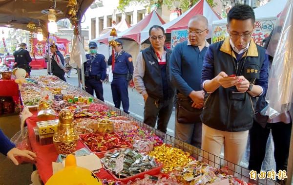 消保官謝明謙(右1)拿起散裝糖果,仔細檢查其商品標示。(記者張菁雅攝)