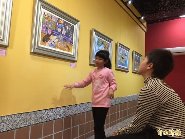 小朋友們在老師的陪同下參觀藝廊,自己的作品放在上頭也有成就感。(記者邱書昱攝)