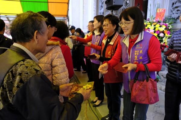 民政局主任秘書王淑貞(右一)等發送紅包給到廟裡拜拜的民眾。(朝元宮提供)