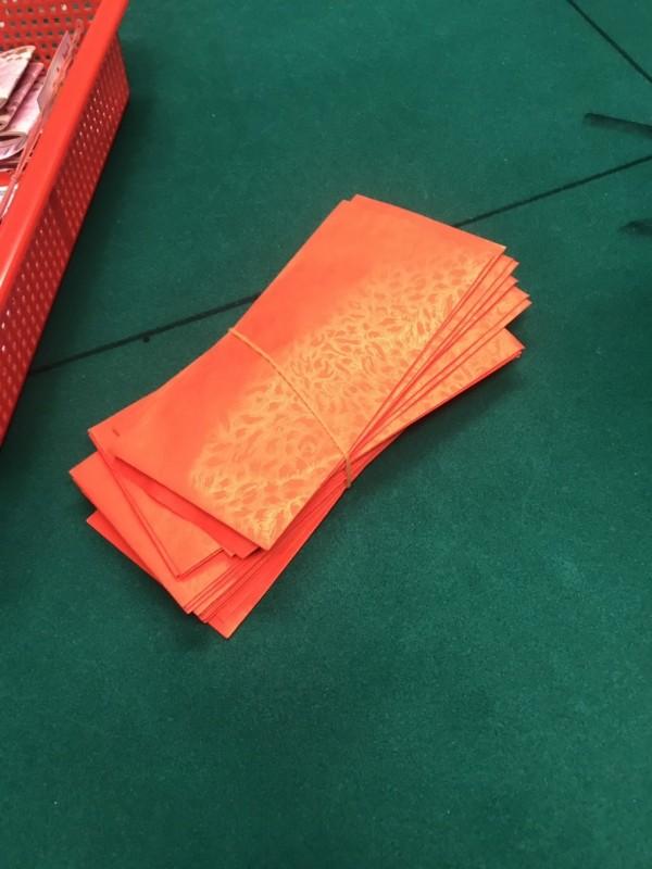 賭場負責人自備紅包、要給來賭場的客人好運。(記者楊政郡翻攝)