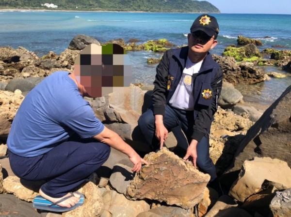 男子將岩石放置在沙灘附近。(記者蔡宗憲翻攝)