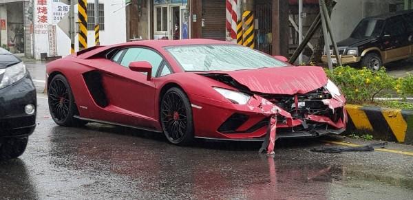 一輛紅色藍寶堅尼「大牛」Lamborghini Aventador,今天上午行經新北市萬里區加投路時,失控自撞安全島,安全氣囊爆開。(擷取自「北海岸全民聯盟公社」)