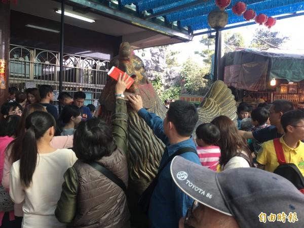 民眾求取財發金後忙著觸碰吉祥金雞。(記者佟振國攝)