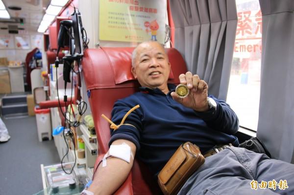 民眾挽袖捐熱血,拿到龍鳳宮媽祖紀念金幣感覺很有福氣。(記者鄭名翔攝)