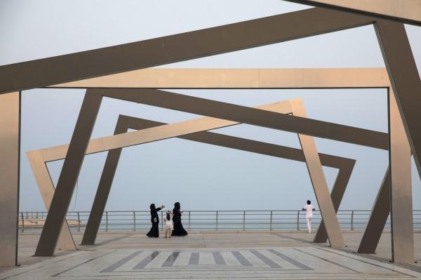 圖為一名沙國男性帶著妻女在沙國境內旅遊。(彭博檔案照)
