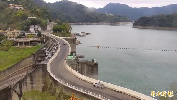 大雨不來石門水庫水位直直落,大壩兩側原本覆蓋水中的岩石已浮出一大截。(記者李容萍攝)