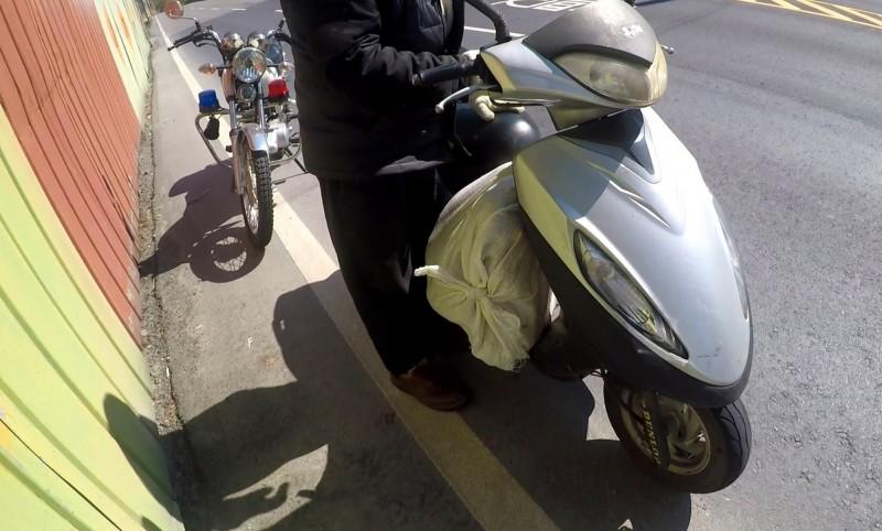 李姓男子把比特犬裝在飼料袋,置於機車腳踏板上運送。(記者陳鳳麗翻攝)