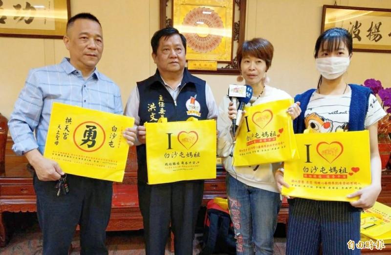 李小姐(右二)母女捐贈2萬個環保袋送給白沙屯媽祖,拱天宮主委洪文華(左二)、雲林至善文化協會執行長蔡銘貴(左一)代表致謝。(記者廖淑玲攝)