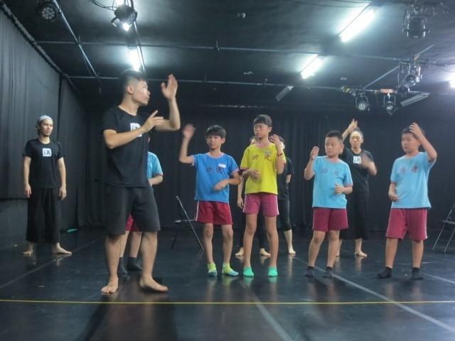 EX-亞洲劇團演員與建功國小學生分享舞龍在劇場中的呈現方式。 (EX-亞洲劇團提供)