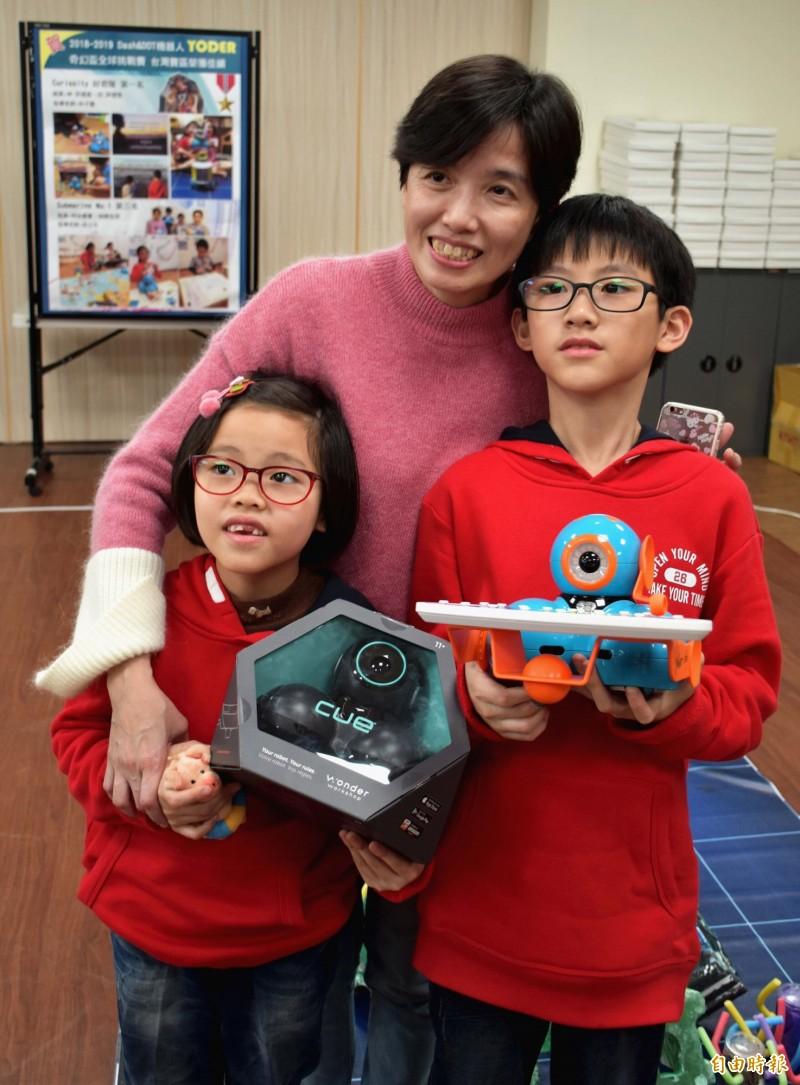 許捷崴、許捷雯小兄妹在媽媽兼教練林子慧指導下,抱回奇幻盃Dash and Dot機器人全球挑戰賽9歲至11歲組冠軍。(記者李容萍攝)