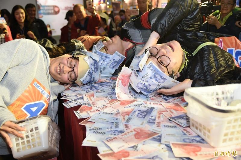 幸運贏得日本來回機票的孫小姐(右一),整個頭部在桌上滾動黏錢。(記者張忠義攝)