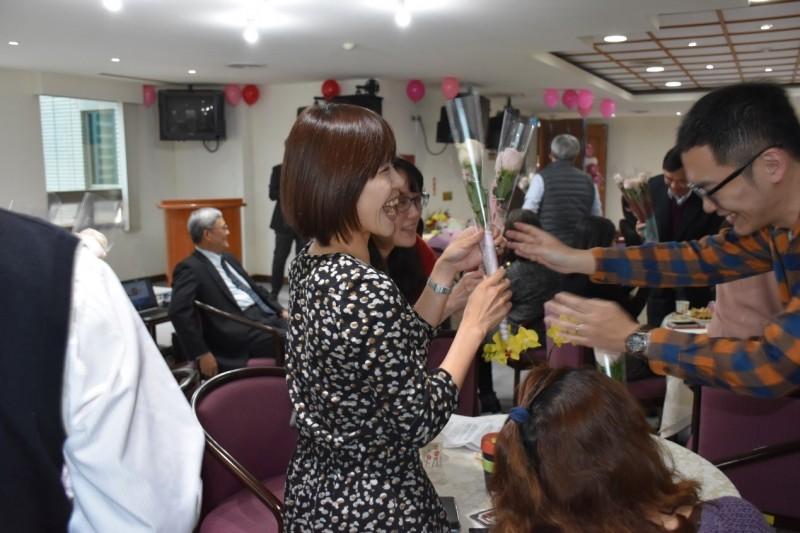 男性同仁送玫瑰花給女同仁,女同仁笑開懷。(記者王俊忠翻攝)
