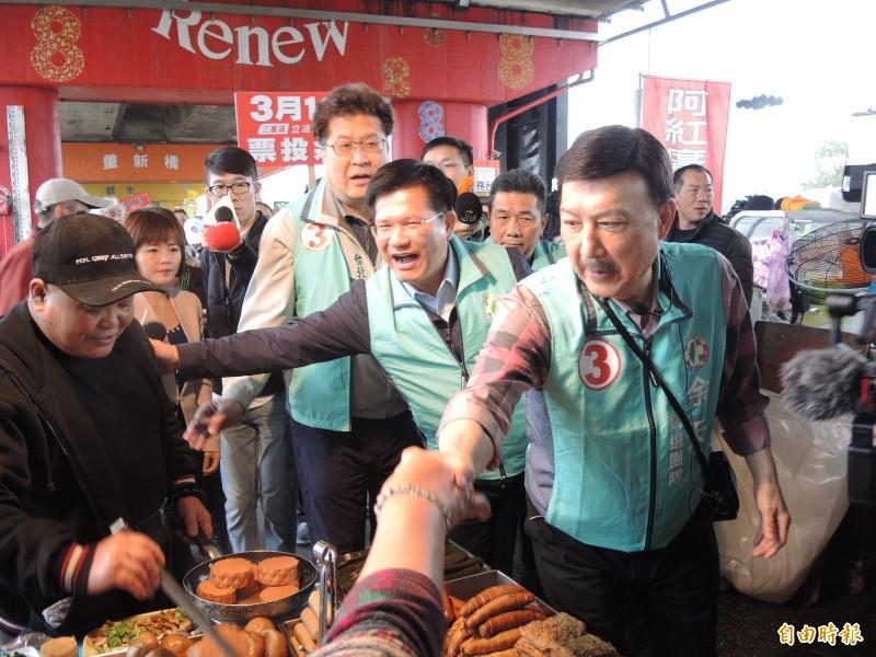 林佳龍(中)陪同余天到重新橋下跳蚤市場拜票。(記者翁聿煌攝)