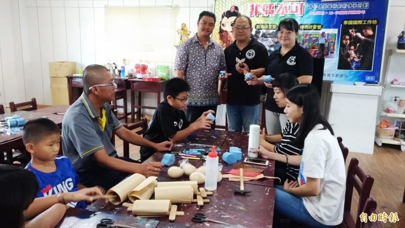 徐建彰(後排中)和家人成立全台第一家布袋戲偶觀光工廠「偶的家」炎卿戲偶文創園區,傳承台灣偶戲文化精髓。(記者廖淑玲攝)