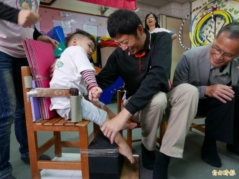 戴啟源與十方啟能中心早療的孩子相見歡,一一與他們擁抱、加油打氣。(記者蔡淑媛攝)
