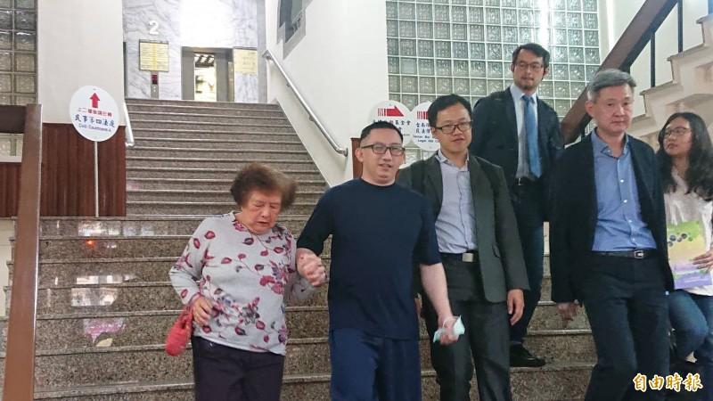 謝志宏開庭結束後在律師團隊陪同下,牽著母親的手走下高分院的台階,迎接相隔19年、6834天的自由。(記者王捷攝)