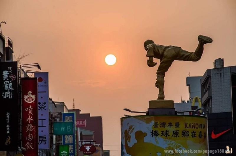 洪年宏結合懸日、吳明捷銅像,拍出如投出好球的美景。(洪年宏提供)