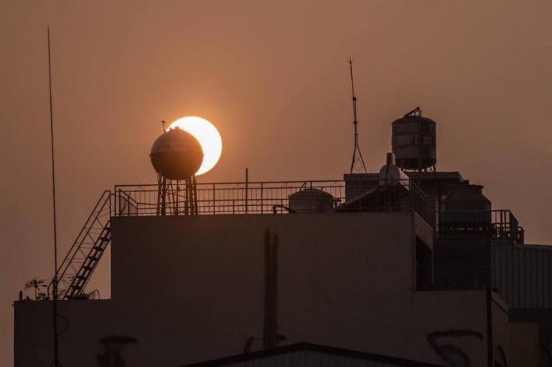 吳居祿建議,也可發揮創意,如將大樓的水塔對準夕陽,拍出如日偏食的不同構圖。(吳居祿提供)