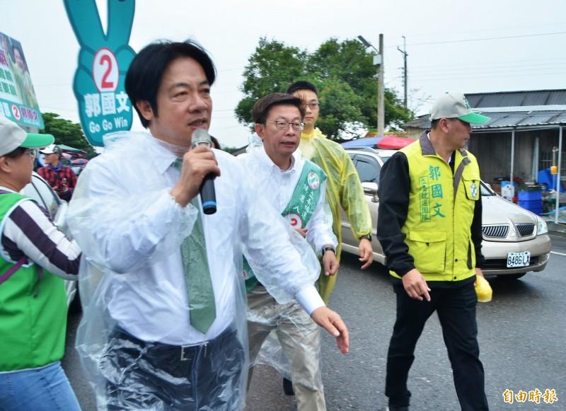 前行政院長賴清德(左)陪同民進黨立委候選人郭國文在善化牛墟冒雨徒步掃街。(記者吳俊鋒攝)