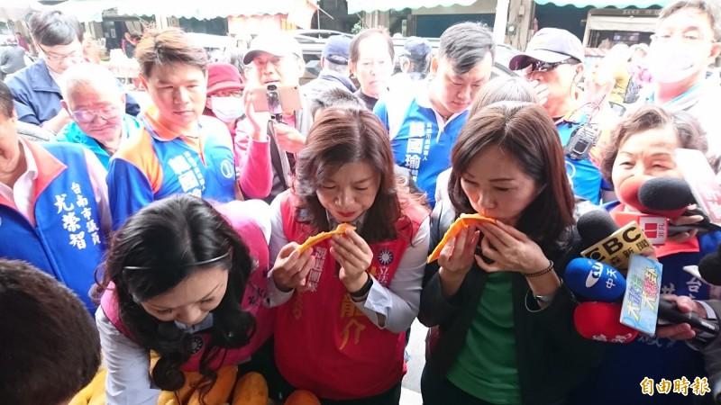 韓國瑜的妻子李佳芬(前右二)和謝龍介的妻子李佳芬(前右三)在麻豆市場買菜吃木瓜。(記者楊金城攝)