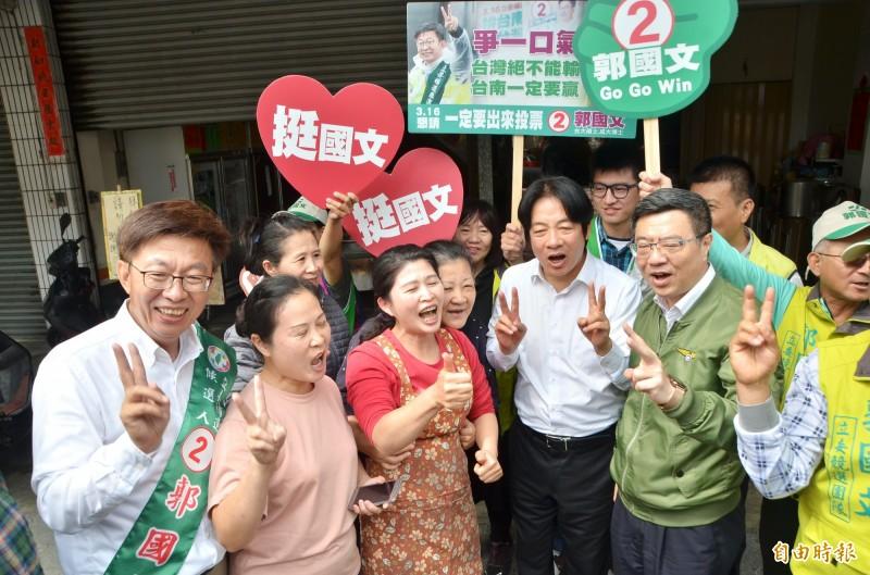 民進黨立委候選人郭國文(左1)掃街拜票,與鄉親博感情。(記者吳俊鋒攝)