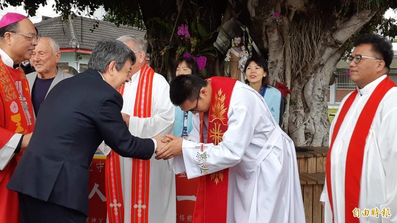 副總統陳建仁(著西裝者)今天出席紀守常神父百歲冥誕彌撒,向神職人員握手。(記者黃明堂攝)
