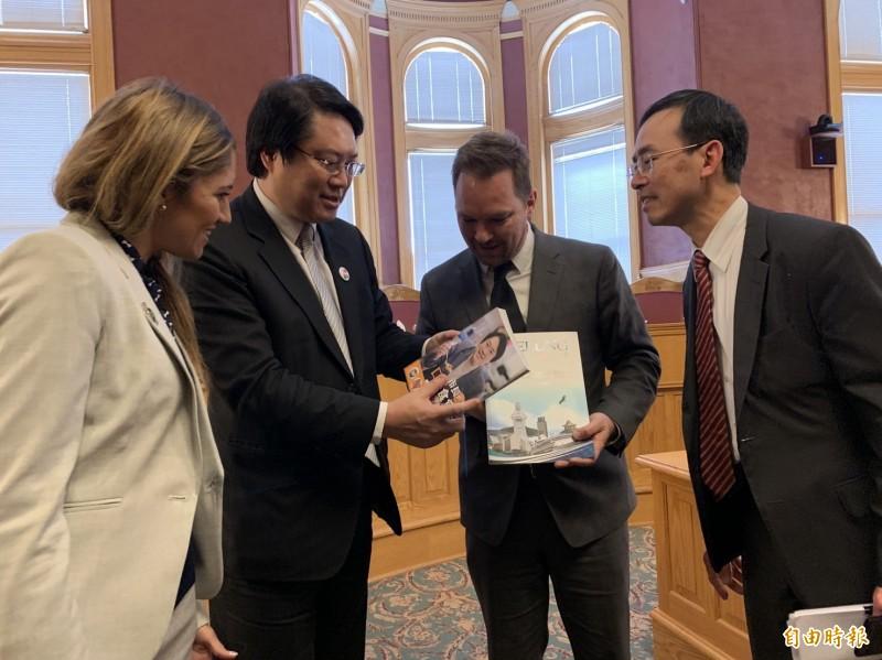 林右昌送他的新書給鹽湖城官員,介紹基隆的美麗與美食。(基隆市政府提供)