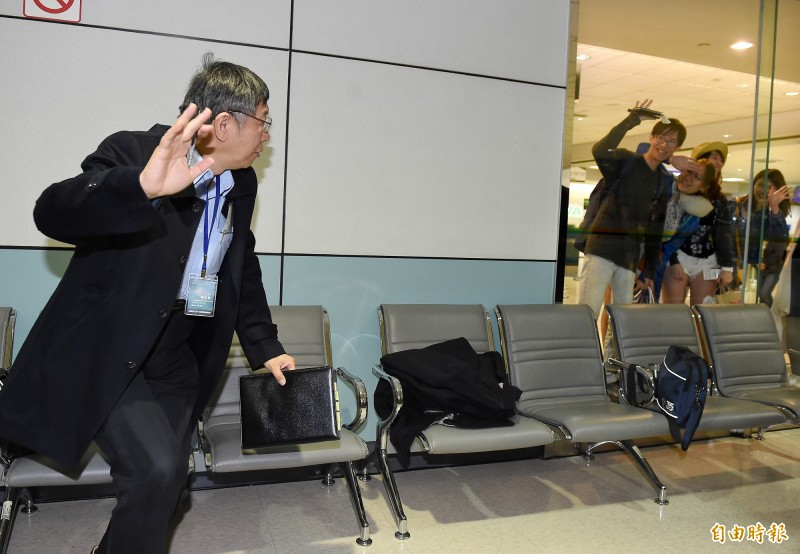 台北市長柯文哲16日晚間啟程展開為期9天的訪美行程。他在候機室等候登機時,隔著玻璃向入境長廊上的旅客揮手致意。(記者朱沛雄攝)