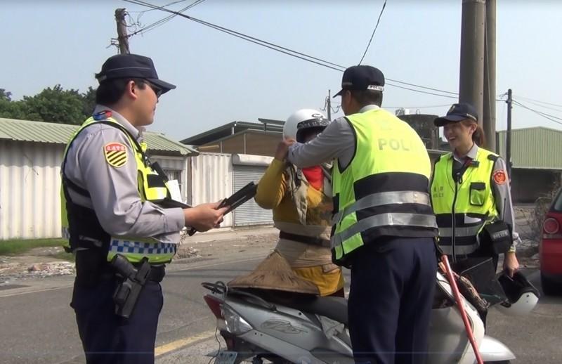 南市交警為未戴安全帽的機車騎士戴上平安帽。(記者王俊忠翻攝)