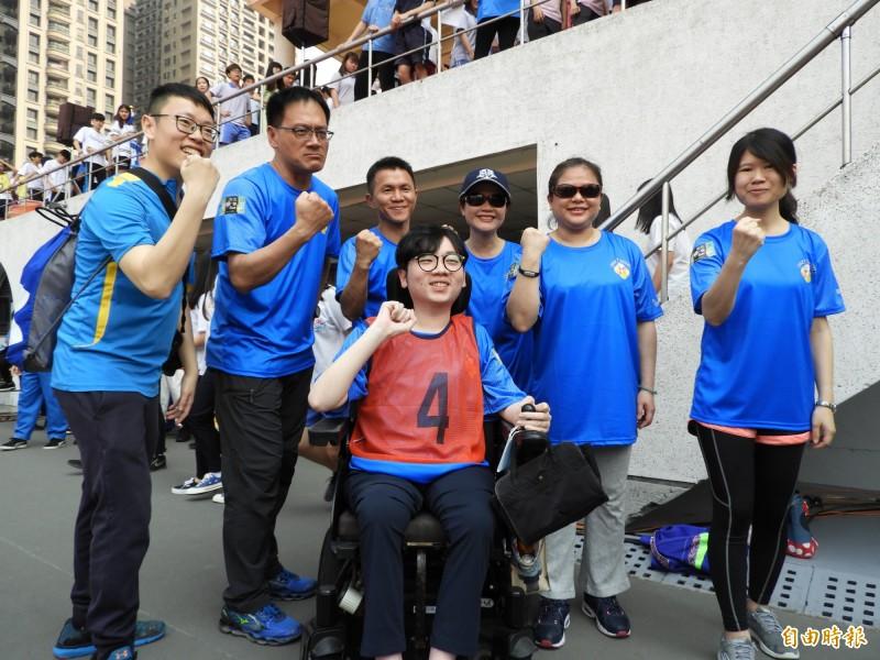 罹患肌肉萎縮症的新北市政府員工陳彥瑀今天參加生平首場大隊接力活動,同事們為他加油。(記者賴筱桐攝)