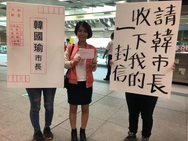 年輕媽媽與同伴手持「請韓市長收下我的一封信」標語。(取自基進黨臉書)