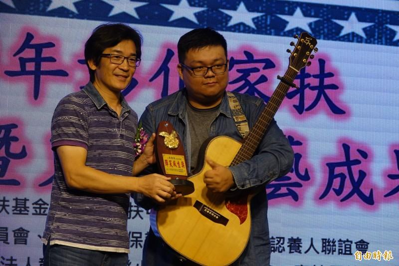 彰化家扶中心的自立青年黃得東,自彈自唱「國境之南」,導演魏德聖(圖左)也頒獎表揚。(記者劉曉欣攝)