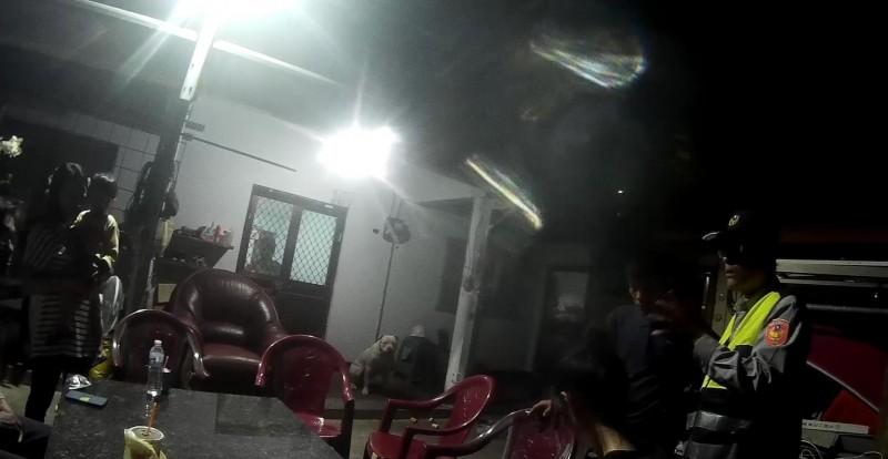 事發當晚,警方到住家了解狀況,只見釀禍的比特犬一臉無辜地在門口角落盯著眾人。(記者王秀亭翻攝)