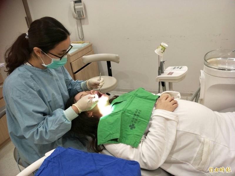 余敏甄醫師幫孕婦檢視口腔狀況。(記者張軒哲攝)