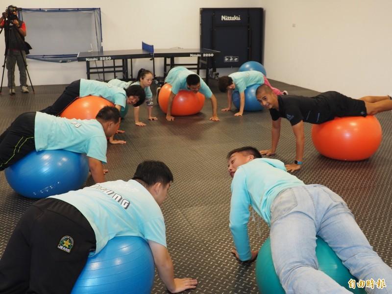 在教練帶領下,學員們利用健身球練習各種動作。(記者王秀亭攝)