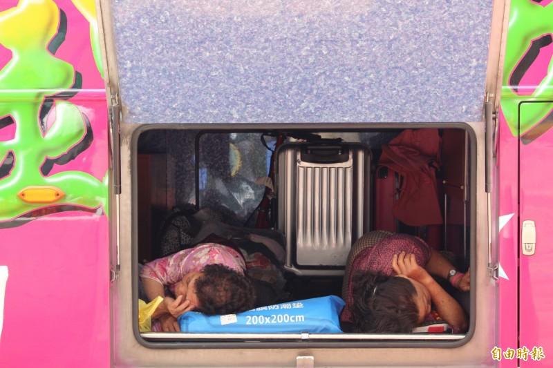 大甲媽遶境進入第2天,信徒走累了就地找地方休息,就連遊覽車行李箱的空間,也變成信徒睡覺打地舖的場地,遊覽車成了另類的「膠囊」旅館。(記者張聰秋攝)