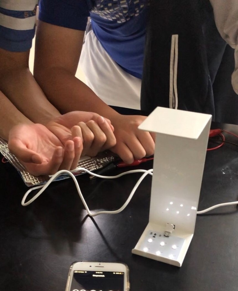 明道中學國際部曹泰然、田紹遠及趙建程三位同學,利用「半導體溫差發電晶片」製作發電系統,以身體熱能就能發電,成功點亮電燈。(記者陳建志翻攝)