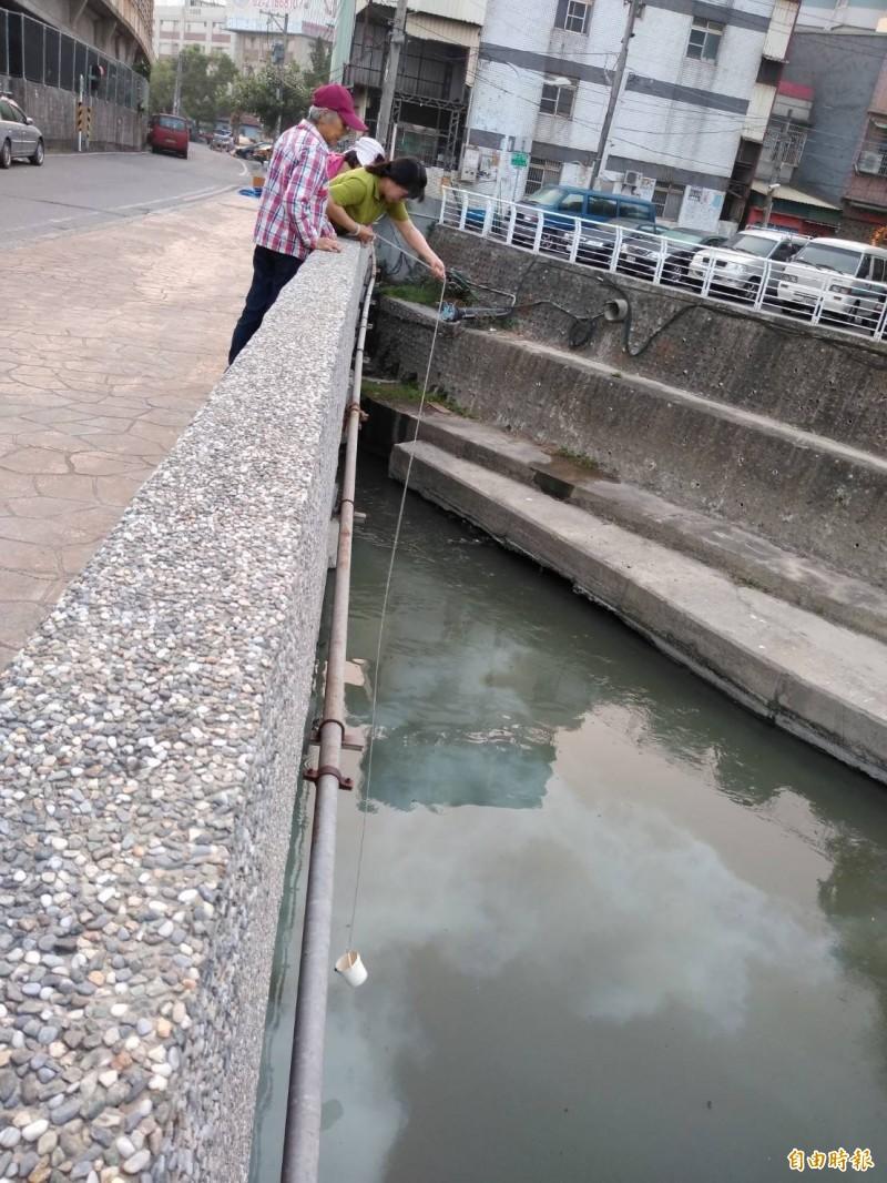 鳳山溪再傳變色,北門里河川巡守隊採集水樣。(記者陳文嬋攝)