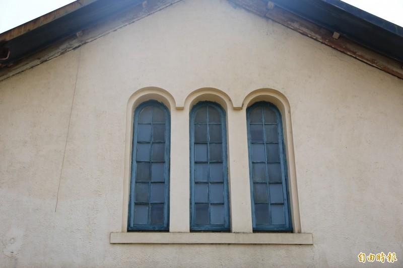 小學校禮堂為鵝黃色磚造建築物,牆面採仿西式左右對稱,木窗均屬疊窗構件。(記者鄭名翔攝)